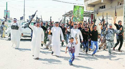 Iraqi Shiite tribal fighters raise their weapons and chant slogans against the Islamic State of Iraq and the Levant in Baghdad. Source: AP