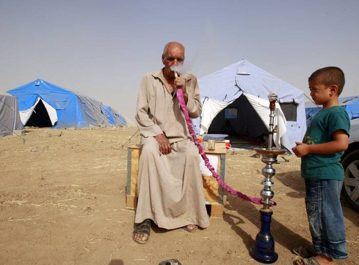An elderly Iraqi refugee smokes a shisha pipe as he sits outside his family's tent at Khazir refugee camp outside Irbil. (Source: AP)