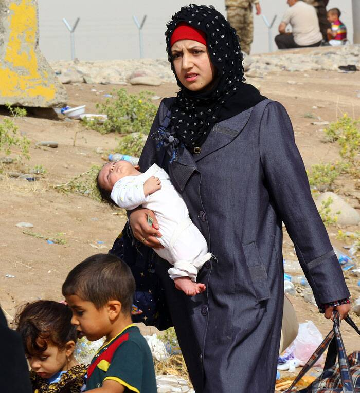 A woman carrying her baby is migrating from her house in Mosul. An estimated half a million residents fled Mosul, the economically important city. (Source:AP)