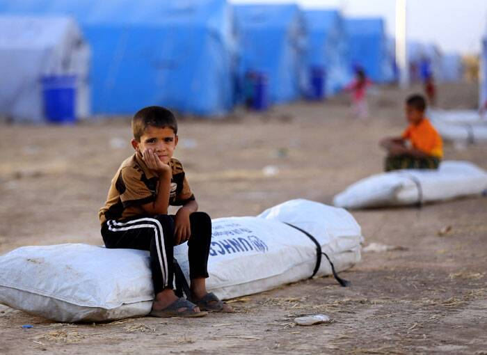 A kid refugee sits outside the tent in refugee camp. (Source: AP)