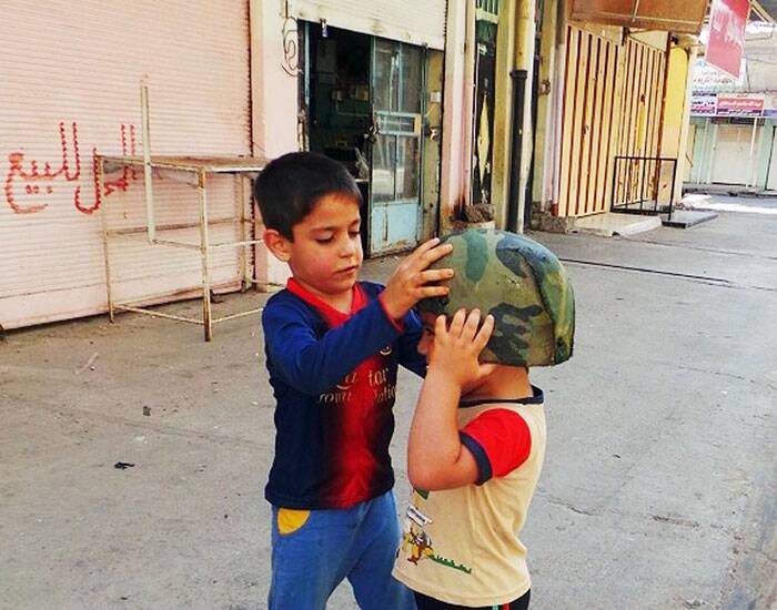 Children play with an Iraqi Army helmet left behind after militants from the al-Qaida-inspired Islamic State of Iraq and the Levant took over the northern city of Mosul. (Source: AP)