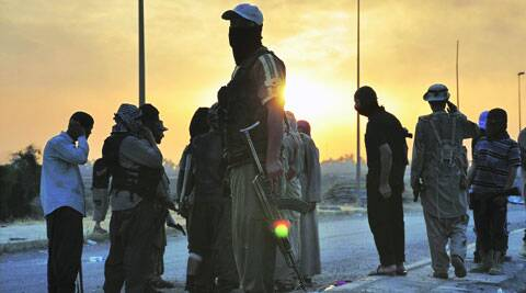ISIS militants stand guard at a checkpoint in the Iraqi city of Mosul, Wednesday. (Source: Reuters photo)