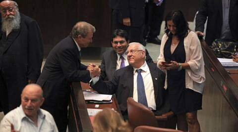 Israeli presidential candidates and former ministers Meir Shitrit, center left, and Reuven Rivlin, center right, shake hands during the Presidential election at the Knesset. (AP)