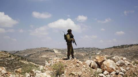 An Israeli soldier stands near the West Bank city of Hebron. (AP)