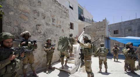 Israeli soldiers patrol during a military operation to search for three missing teenagers outside the West Bank city of Hebron. (AP)