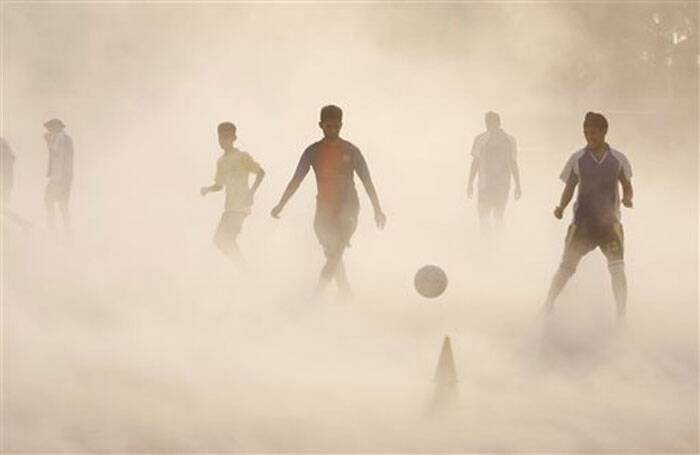Undeterred by a ragin dust storm, aspiring young Indian football players continue with their practice in Jammu, India. Indian football fans will be following the World Cup with great zeal and enthusiasm. (Source: AP)