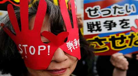 """A protester wears a hand-shaped mask reading: """"Stop Wars"""" during a rally in front of the Japanese prime minister's official residence in Tokyo. (Source: AP)"""