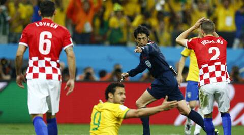 Referee Yuichi Nishimura (C) of Japan gestures for a penalty during the  opening match between Brazil and Croatia. (Source: Reuters)