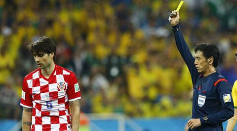 Croatia's Vedran Corluka is shown the yellow card by referee Yuichi Nishimura of Japan. (Source: Reuters)