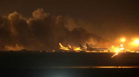 Fire illuminates the sky above Karachi airport terminal where security forces are fighting with attackers Sunday night. (Source: AP)