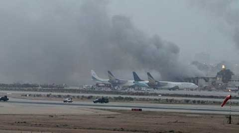 Smoke rises above the Jinnah International Airport where security forces continue to battle militants Monday. (Source: AP)