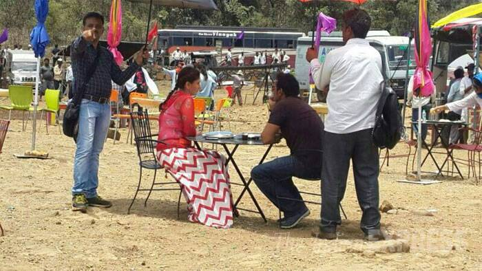 Kareena and Ajay sit at a table surrounded by their crew as they shoot a scene. (Source: Varinder Chawla)