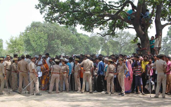 The two girls, who were cousins and aged 14 and 15, went missing from their house on the night of May 27 and their bodies were found hanging from a mango tree in the village in Ushait area on May 28.<br />Policemen cordon off the area as villagers and others look towards the tree where two teenage girls were found hanging after they were gang raped in Katra village in Uttar Pradesh. (Source: AP)
