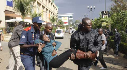 In this Saturday, Sept. 21, 2013 file photo, a security officer helps a wounded woman outside the Westgate Mall after gunmen threw grenades and opened fire during an attack that left multiple dead and dozens wounded. (AP)
