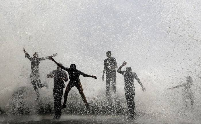 People are seen enjoying high tide waves on the Arabian Sea coast in Mumbai. (Source: PTI)
