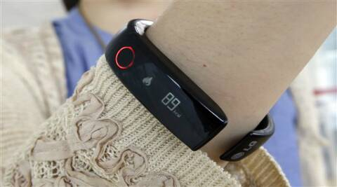 A reporter shows LG's Lifeband Touch for photographs in Seoul, South Korea. LG Electronics Inc. (Source: AP)