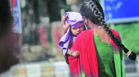 A woman shields her child from the sun and heat on Friday.     ( Express Photo: Oinam Anand)