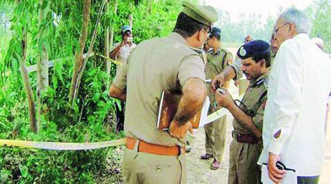 Police inspect  the spot where the body of a  19-year-old girl was found hanging from a tree at Rajupur Milak village in Moradabad Thursday. ( Source: PTI )