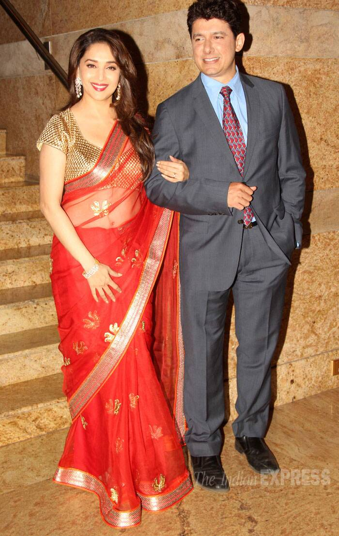 Bollywood's dancing queen Madhrui Dixit was beautiful and radiant in a red SVA sari with a gold blouse as she posed for pictures along with husband Dr. Sriram Nene. (Source: Varinder Chawla)