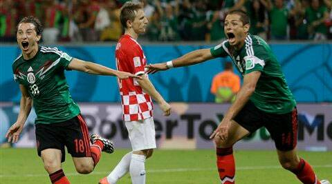 Mexico's Andres Guardado, center, celebrates with Mexico's Javier Hernandez, right, after he scored his team's second goal during the group A World Cup soccer match between Croatia and Mexico. ( Source: AP )