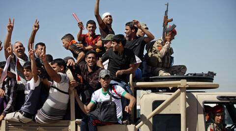 Iraqi men flash victory signs as they leave the main recruiting center to join the Iraqi army in Baghdad, Iraq. (Source: AP)