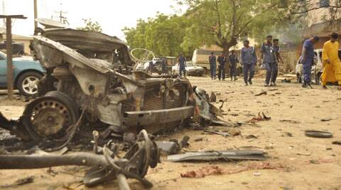 People walk past the remains of a car used for a suicide bomb in Kano, Nigeria. (Source: AP)