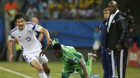 Nigeria's Michael Babatunde is fouled by Bosnia's Mensur Mujdza (L) as Nigeria's coach Stephen Keshi (R) watches (Source: Reuters)