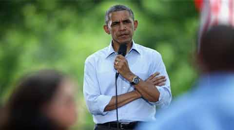 President Barack Obama listens to a speaker at an invite-only town hall meeting at Minnehaha Park in Minneapolis.