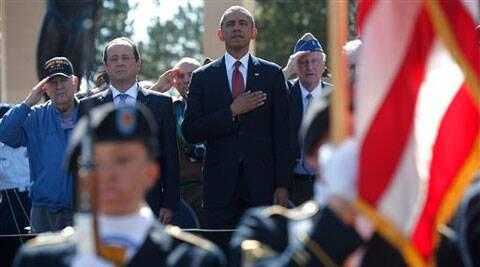U.S. President Barack Obama, centre and French President Francois Hollande stand, during the playing of the Star Spangled Banner, at Normandy American Cemetery at Omaha Beach in Normandy, France on Friday. (Source: AP)