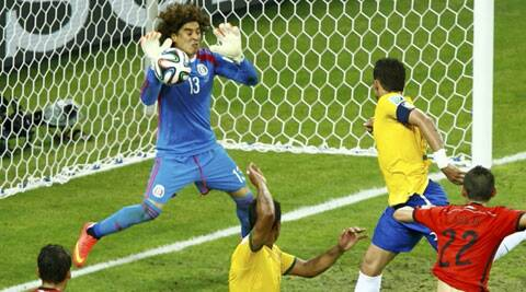 Mexico's Guillermo Ochoa (L) deflects the ball during a goal attempt by Brazil's Thiago Silva (top R) during their 2014 World Cup Group A soccer match at the Castelao arena in Fortaleza (Source: Reuters)