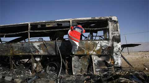 An emergency personnel worker climbs up the side of a burnt-out bus, as he searches for victims of a car bomb explosion in Quetta. (Source: Reuters)