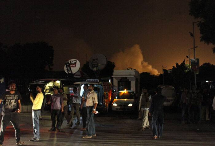A major fire rose from the airport, illuminating the night sky in an orange glow as the silhouettes of jets could be seen. <br /><br /> Reporters stand outside Karachi airport terminal building where security forces were engaged ina gun fight with attackers on Sunday night, June 8, 2014, in Pakistan. (AP)