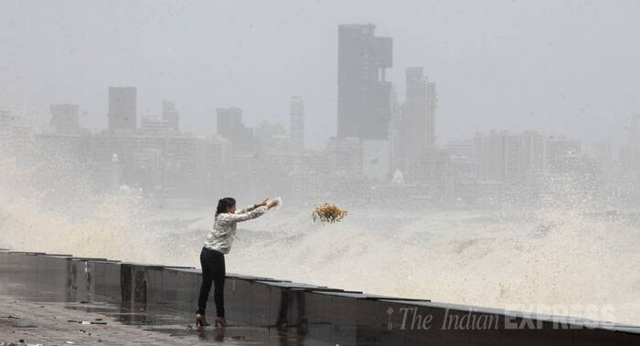 A woman flings over some garbage into the lashing waves. (Source: Express Photo by Prashant Nadkar)