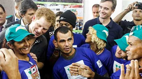 "Britain's Prince Harry, top left, speaks with people who take part in a social project that aims to reduce drug addiction in an area known as ""Crackland"" in Sao Paulo, Brazil. (AP Photo)"