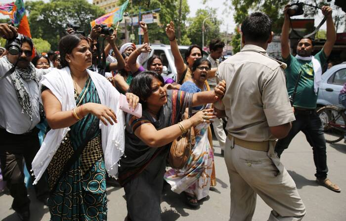 A BJP member pushes aside a policeman blocking the path during a protest against the gang rape of two teenage girls, in Allahabad. (Source: AP)