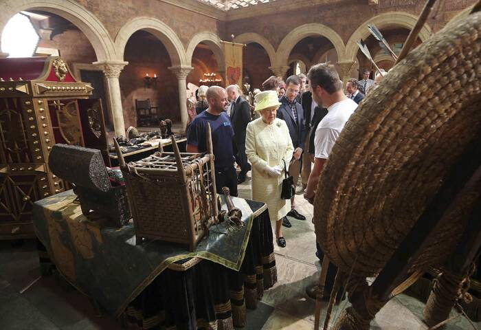 Queen Elizabeth looks at props during her visit to the set of the television series Game of Thrones. (Source: Reuters)