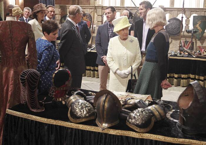 Queen Elizabeth talks to an unidentified guest as she looks at props on the sets of Game of Thrones. (Source: Reuters)