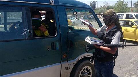 A fighter with the al-Qaida-inspired Islamic State of Iraq and the Levant (ISIL) distributes a copy of the Quran, Islam's holy book, to a driver in central northern city of Mosul. Source: AP