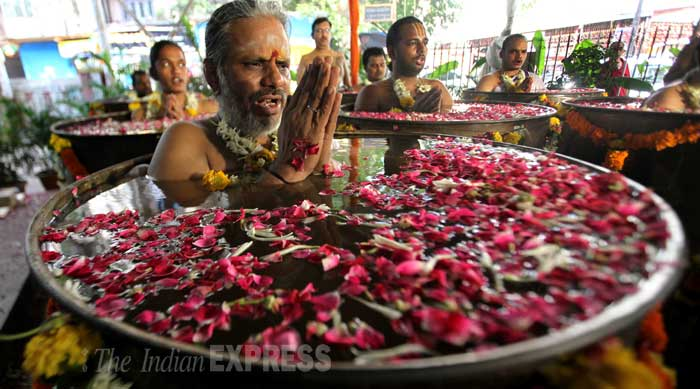 Priests sit inside water barrels as they perform special prayers in order to appease Varun, the Hindu rain god, in a temple in Mumbai. (Source: Express photo by Pradeep Kocharekar)