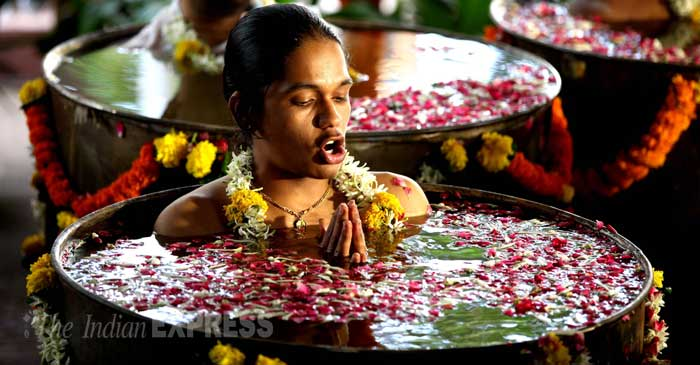 A priestess chants a mantra submerged in water during the puja. (Source: Express photo by Pradeep Kocharekar)