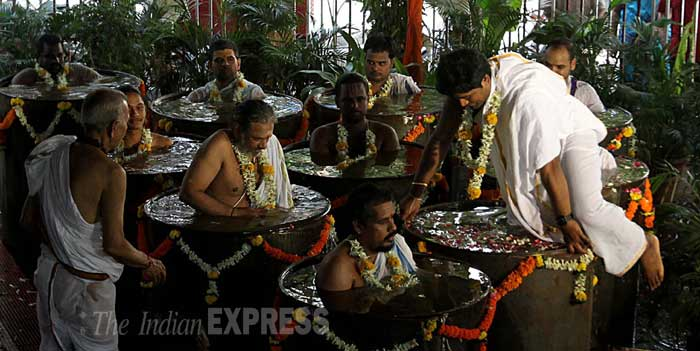 A priest gets inside a barrel to join his colleague in the puja (Source: Express photo by Pradeep Kocharekar)