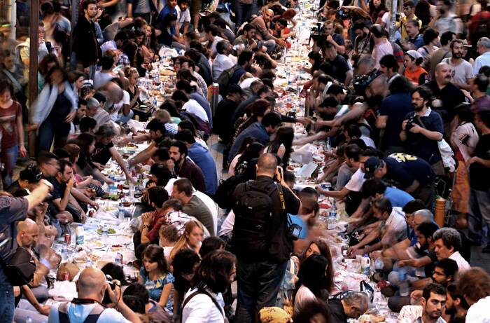 Ramzan, the ninth month of the Islamic lunar calendar, is observed as a fasting period by Muslims, who abstain from food and water from sunrise to sunset.<br /><br />Hundreds of people sit, awaiting for Iftar, the evening meal in which Muslims break their fast at the time of sunset, during Ramzan in Istanbul, Turkey. (Source: AP)
