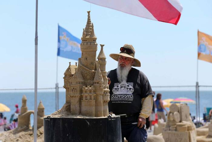 Rich Varano, of New Smyrna Beach, poses with his sand creation during the competition. (Source: AP)