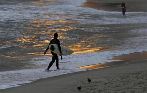 A surfer walks along Ipanema Beach in Rio de Janeiro June 4, 2014. Source: Reuters