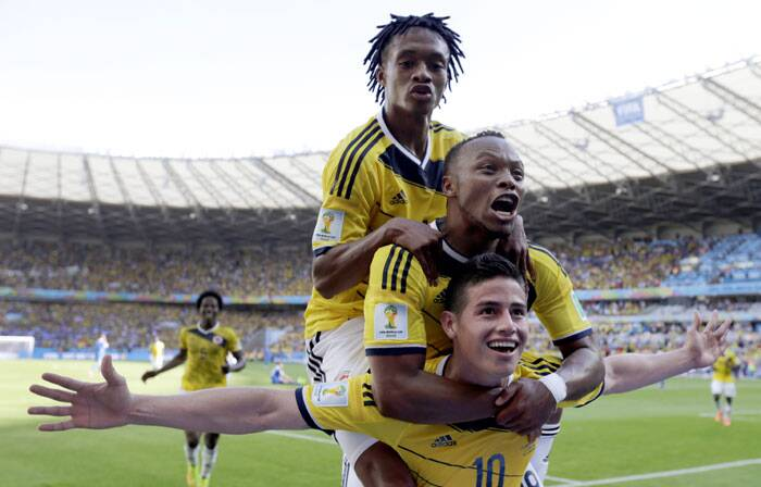 Tower of joy: James Rodriguez is jumped on by teammates after scoring Colombia's third goal in the dying minutes of the game against Greece. (Source: AP)