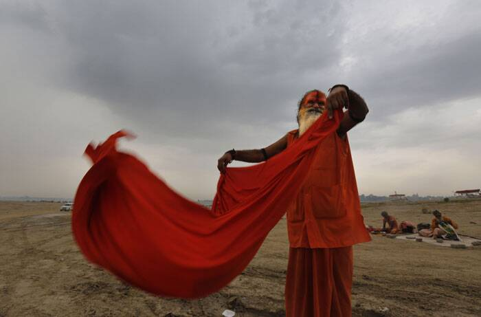 A Hindu devotee dries his cloth after taking  ritualistic holy dip at Sangam. (Source: AP)