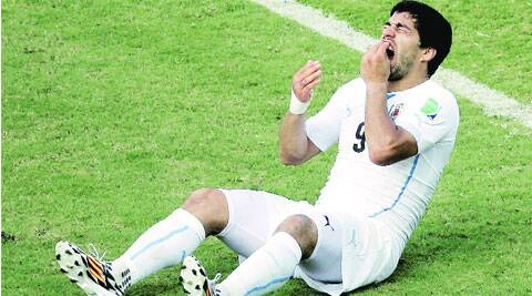 Luis Suarez holds his teeth after the alleged bite.