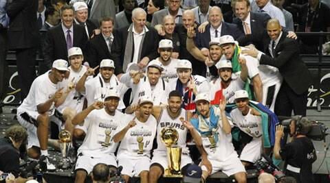 San Antonio Spurs' Tim Duncan (C, front) sits with the Larry O'Brien trophy and teammates after the Spurs defeated the Miami Heat in Game 5 of their NBA Finals (Source: Reuters)