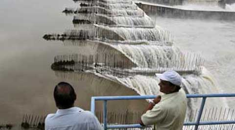 Officials look at the overflowing Sardar Sarovar dam. (Source: Reuters)