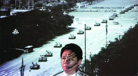 Sin Wai-keung, a former news photographer, poses in front of a projection of a photograph he took in Beijing in 1989. Sin's photo shows a man standing in front of a column of tanks in Beijing on the morning of June 5, 1989. REUTERS